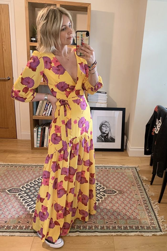 best floral dresses: Emma Rose Thatcher wearing a yellow and purple floral wrap dress