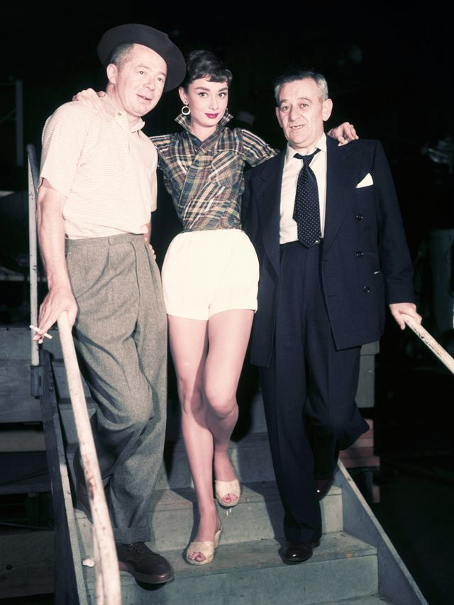 Style Notes: Ignore the two Hollywood chaps flanking Audrey Hepburn, and focus in on her artfully wrapped shirt, tucked into high-waisted shorts and styled with mules. This is a simple outfit you...