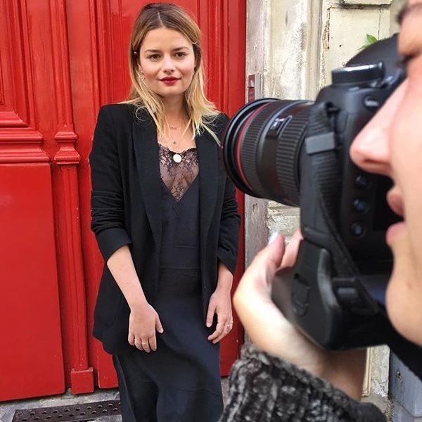 French fashion journalist Sabina Socol looks impossibly elegant in a black lace slip dress, blazer, and her omnipresent gold circle pendant.