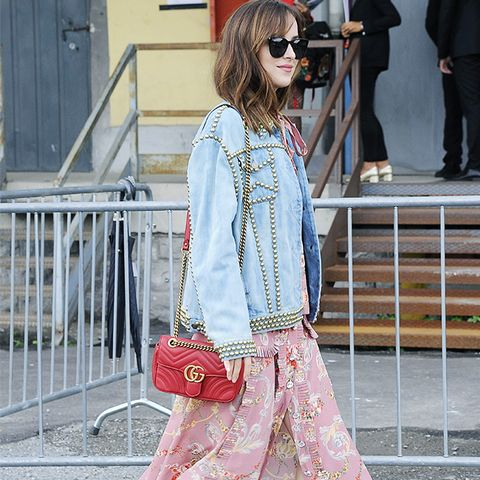 Dakota Johnson Style: Wearing a Gucci denim jacket, floral pink dress and Gucci bag and boots