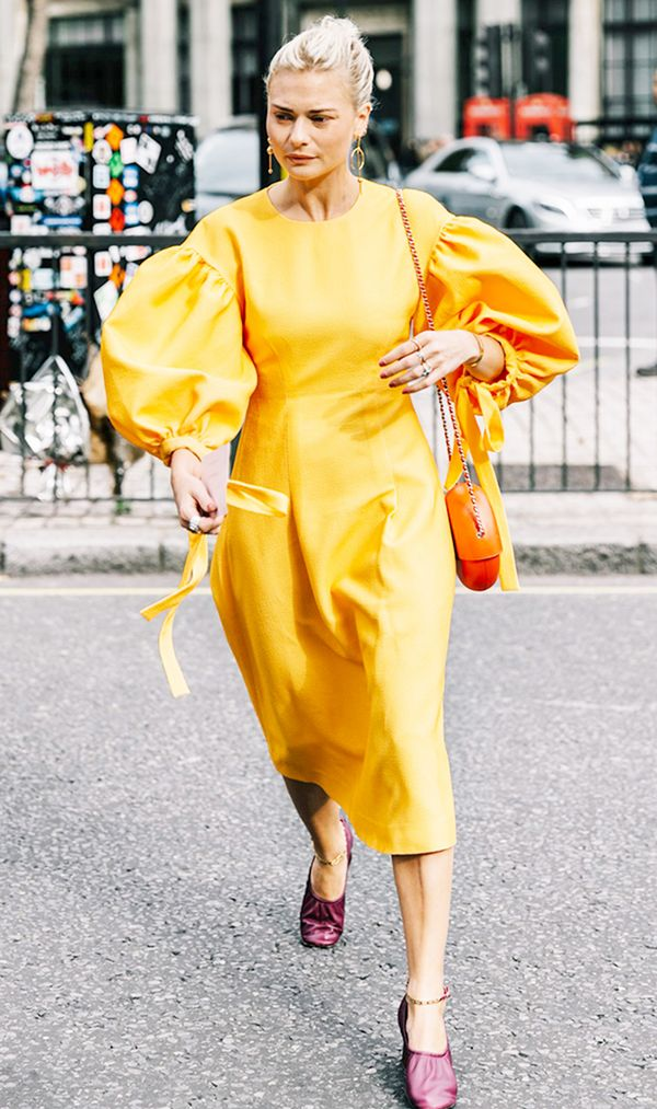 Wear a yellow dress with dramatic balloon sleeves. Style it with simple jewelry, easy slides, and a classic purse.