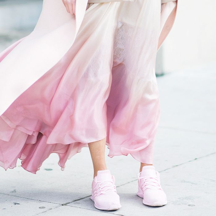 Pink sneaker trend: woman wearing pink trainers and a pink skirt