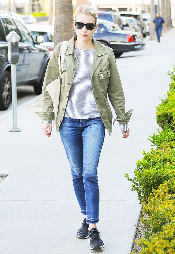 Look no further for the ideal weekend errands outfit than Emma Roberts in an army jacket layered over a classic Breton shirt and finished off with blue jeans and sneakers.