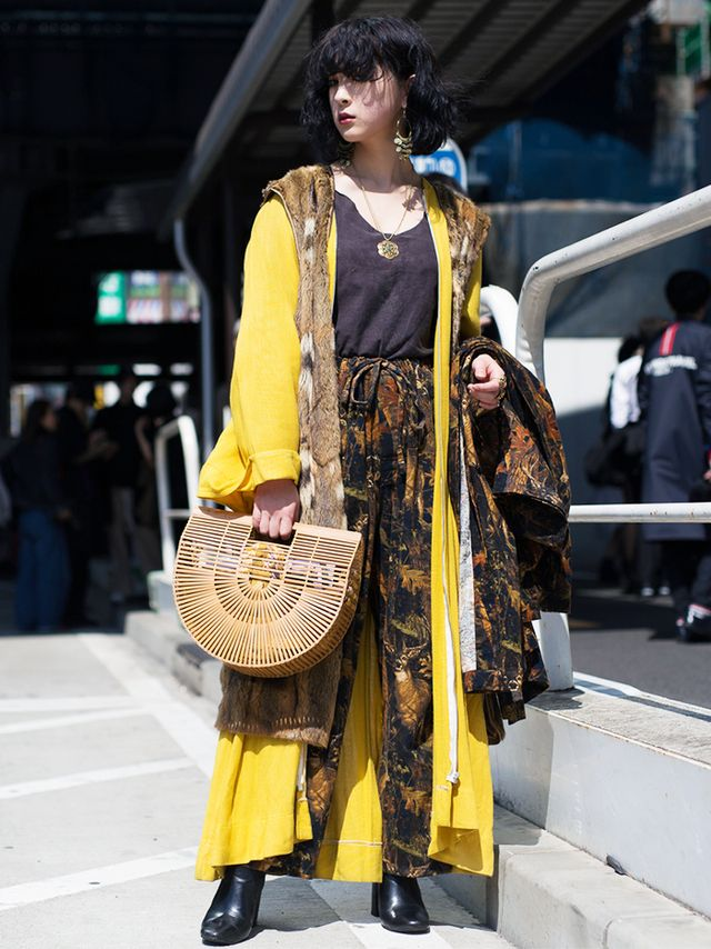 "It would be an understatement to reduce this floor-length canary yellow duster to a ""pop of primary color."" Paired with the unexpected textures of a fur under layer, a bamboo handbag, and bold..."