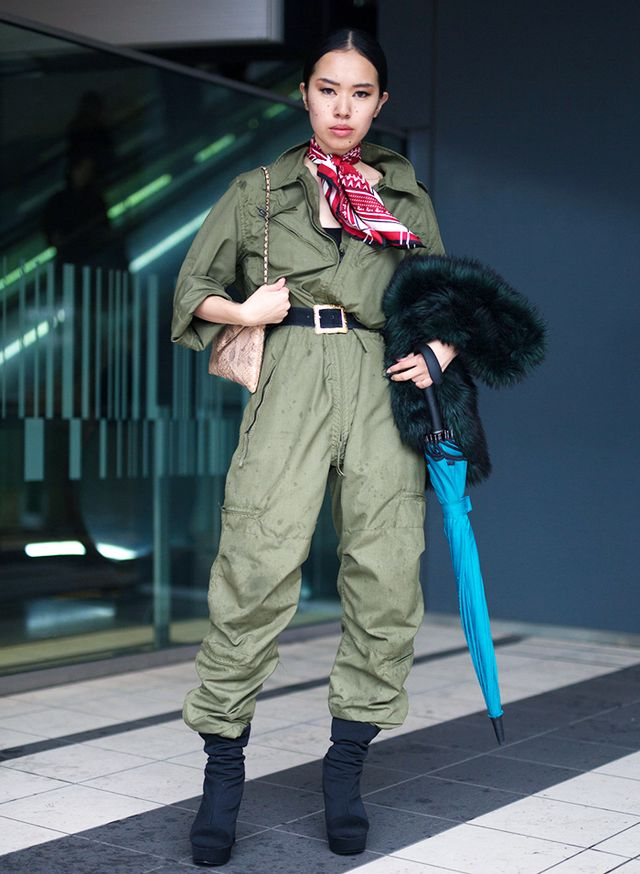 A true jumpsuit, the head-to-toe khaki look is livened up by a pop of primary color via the patterned silk scarf worn as a neckerchief. The jumpsuit's large fit is made chic with a black belt tied...