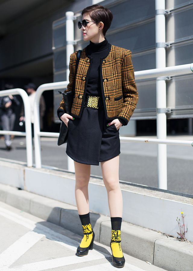 A tweed jacket and Mary Janes worn with socks make this ensemble wonderfully retro, but the bright pop of yellow and round sunglasses keep the look forward-thinking and cool.