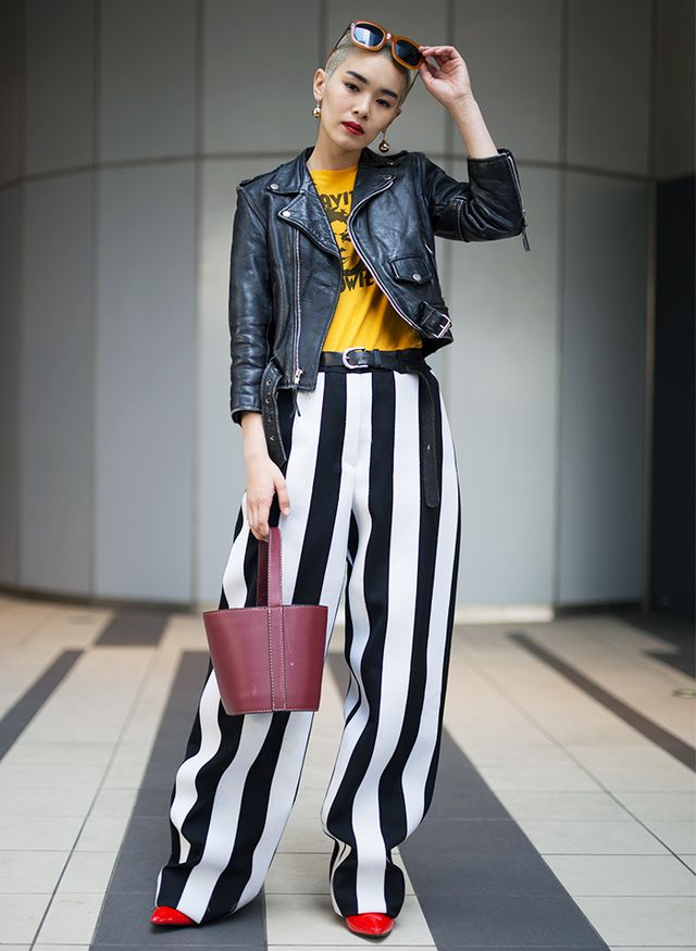 This bold outfit features two of Tokyo's big trends—oversize bottoms with wide-leg striped pants and pops of primary colors, and yellow graphic T-shirts balanced out by a bold red lip and...