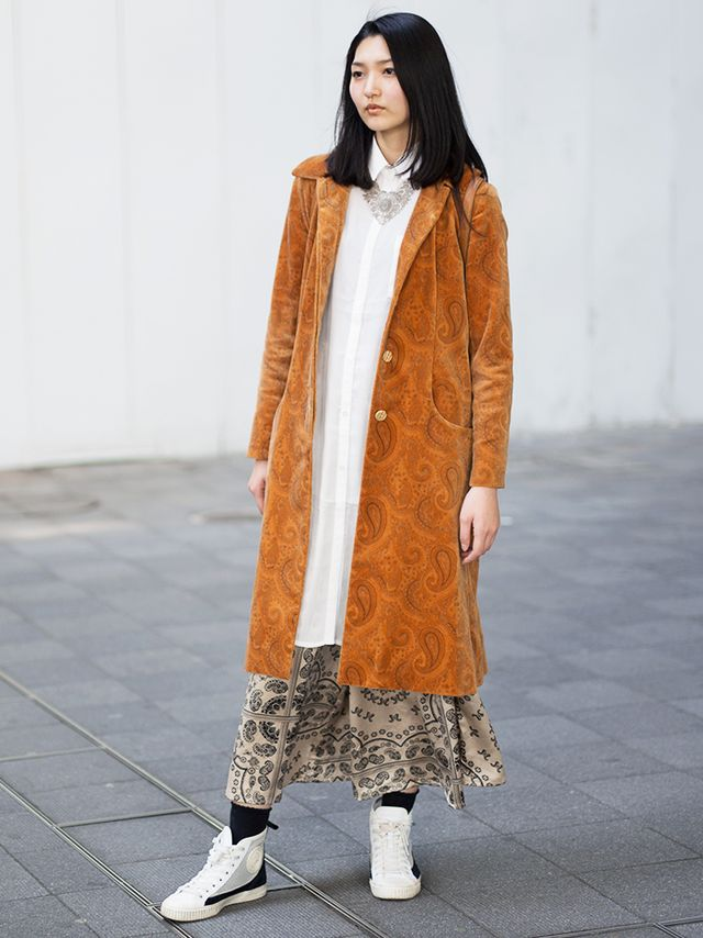 Unexpected textures combine with sneakers and athletic socks to create an eclectic ensemble. The look plays with proportions by incorporating a long paisley patterned coat with a...