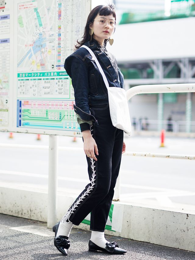 Elizabethan-esque black leather pointed-toe shoes get even funkier when they're worn with white socks and paired with lace-up pants and a cropped denim jacket with statement detailing.