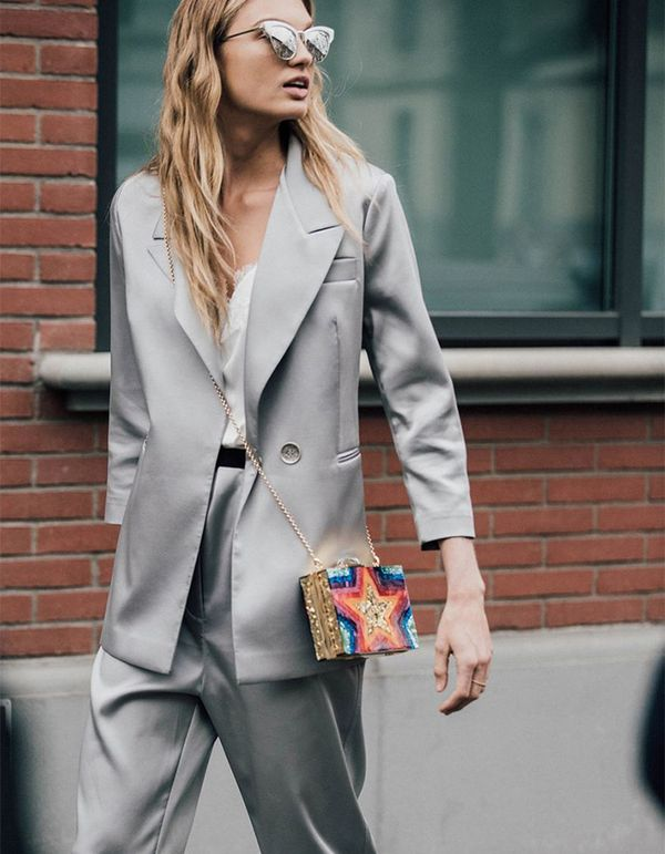 The banker's-gray suit is reimagined in light, luxe fabrics and a flowy silhouette. Take your power suit to new heights by pairing it with a bold and colorful clutch and striking silver sunglasses.