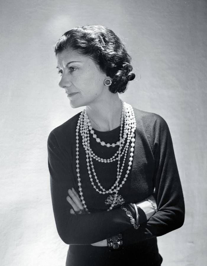 The Story Behind the Chanel Logo: Coco Chanel wearing her signature pearls