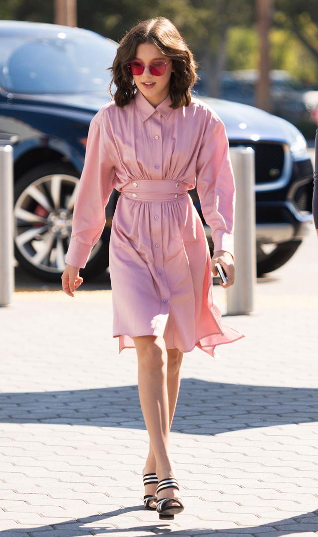 On Millie Bobby Brown: Sies Marjan dress; Alumnae shoes Similar Styles: Ray-Ban Mirrored Rimless Sunglasses ($195); Sies Marjan Ruffle Sleeve Dress ($1295); Alumnae Stitched Mignon Slide ($475)