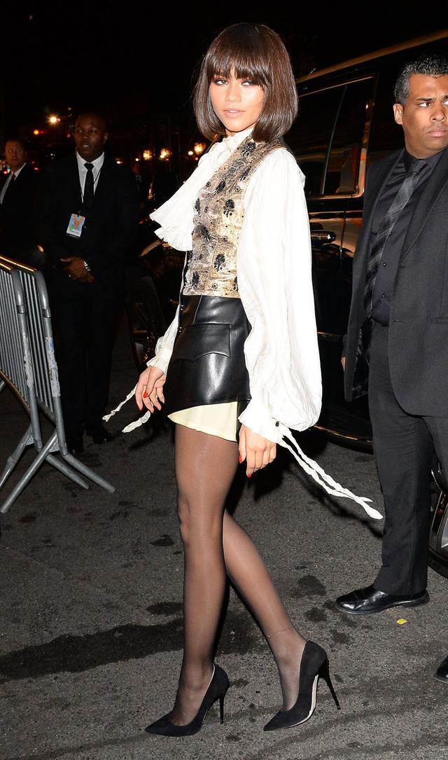 On Zendaya: Louis Vuitton S/S 18 look Similar Styles: Frame Bow-Embellished Chiffon Blouse ($275); Marni Brocade Top ($185); H&M Patent Skirt ($25); Zara Basic Tights ($16); Saint Laurent Anja...