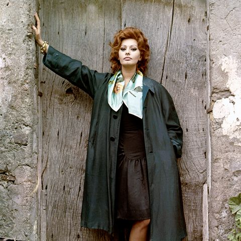 sophia loren style: on the set of Marriage Italian Style, loren looks chic in a big coat, black dress, and scarf