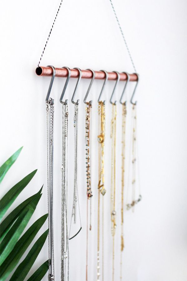 Try this DIY necklace holder. Made from a metal pipe with silver hooks, this necklace storage adds a modern industrial vibe.
