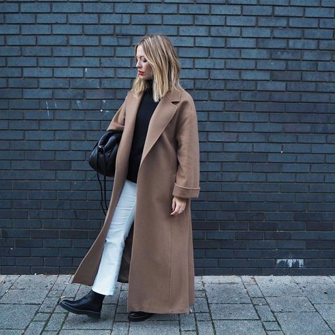 what to wear in December: Alexis Foreman wearing a camel coat and white jeans