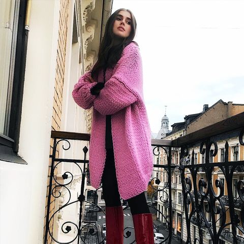 what to wear in December: Darja Barannik in a pink cardigan and red knee-boots