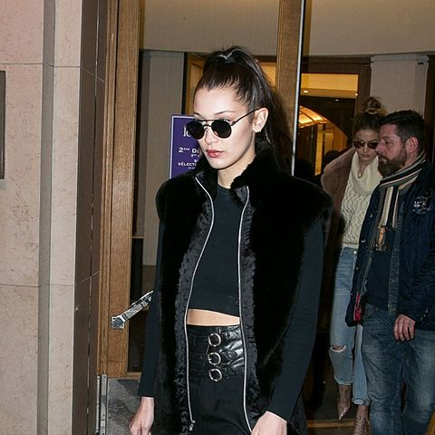 Bella Hadid Wears Black Jacket, Mini Skirt, and Lace Up boots