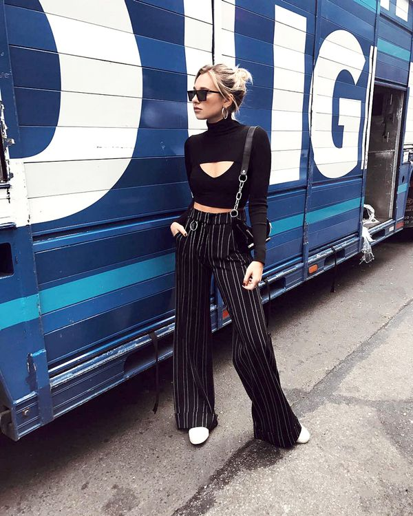 Yes, you can wear sneakers on a night out—this look proves it. Balance out a crop top with an edgy pair of wide-leg pants. Bonus points for a cool, of-the-moment fanny pack.