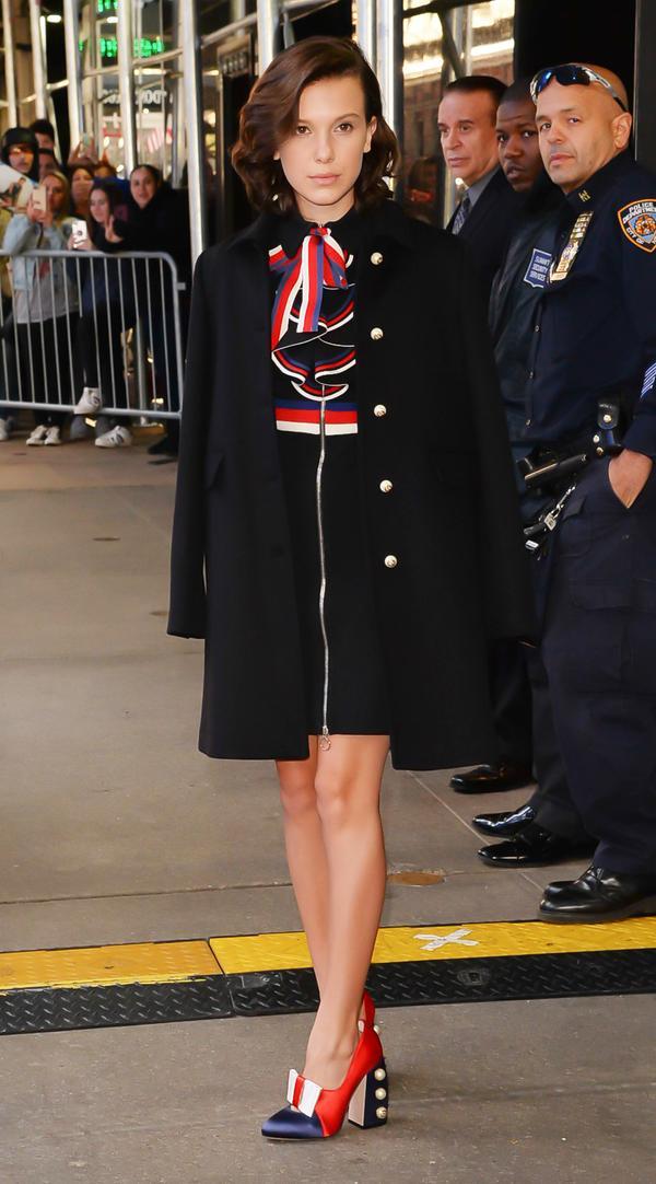 On Millie Bobby Brown: Gucci Sylvie Web Stretch Jersey Dress($1800) andSatin Studded Pump($1150)