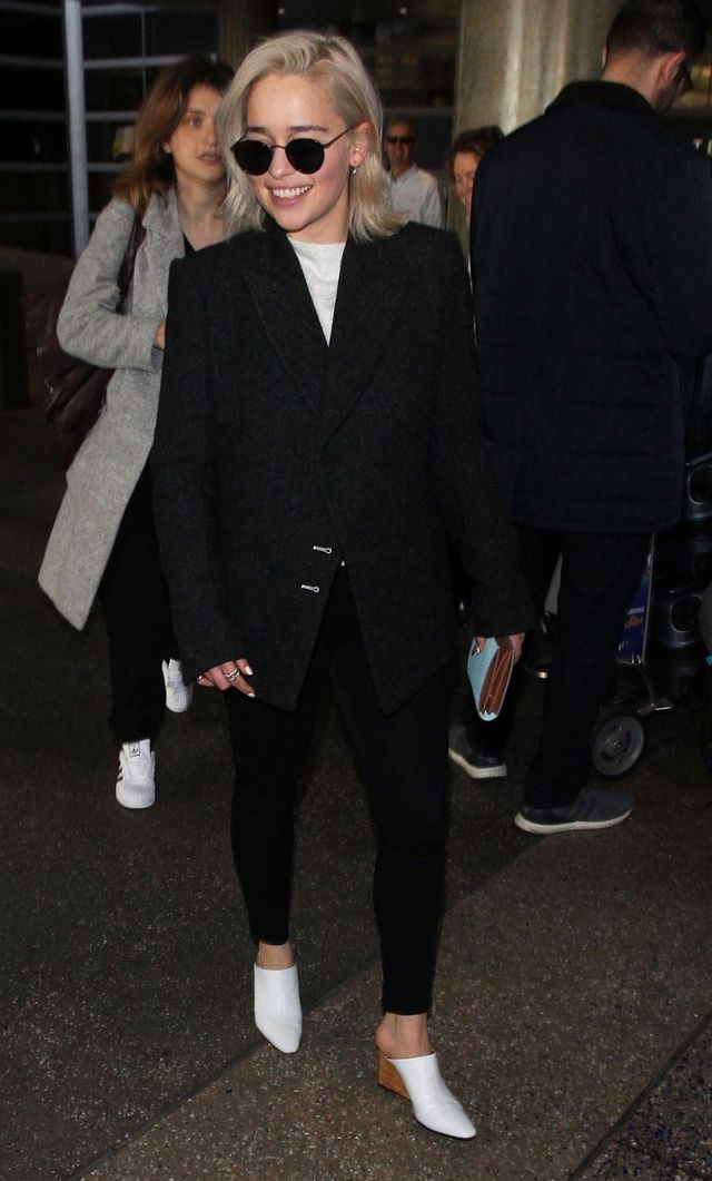 "On Emilia Clarke: The Row Flora Wedge Mules ($990); Oliver Peoples MP-2 Matte Black Sunglasses ($455) Similar Styles: H&M Oversized Jacket ($50); Madewell 9"" High-Rise Skinny Jeans in Black..."