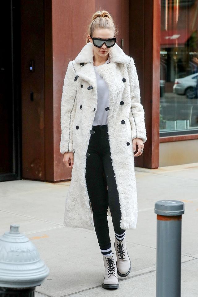 Gigi Hadid wearing combat boots and white coat