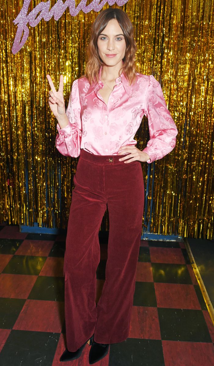 Alexa Chung wearing a pink satin shirt and corduroy trousers