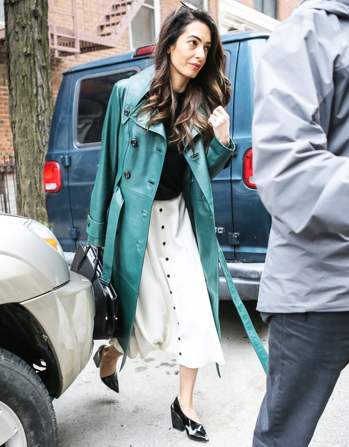 Amal Clooney wearing a green Michael Kors trench coat, white Emilia Wickstead skirt, Dior bag and Peta Petrov patent shoes to Columbia Law School in NYC