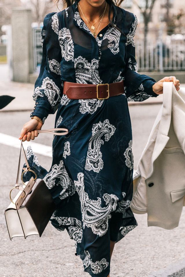 A simple brown leather belt grounds a flowing patterned dress.