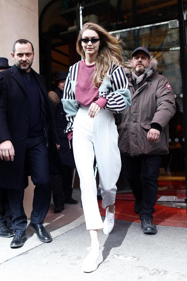 Gigi Hadid in a striped sweatshirt and white pants