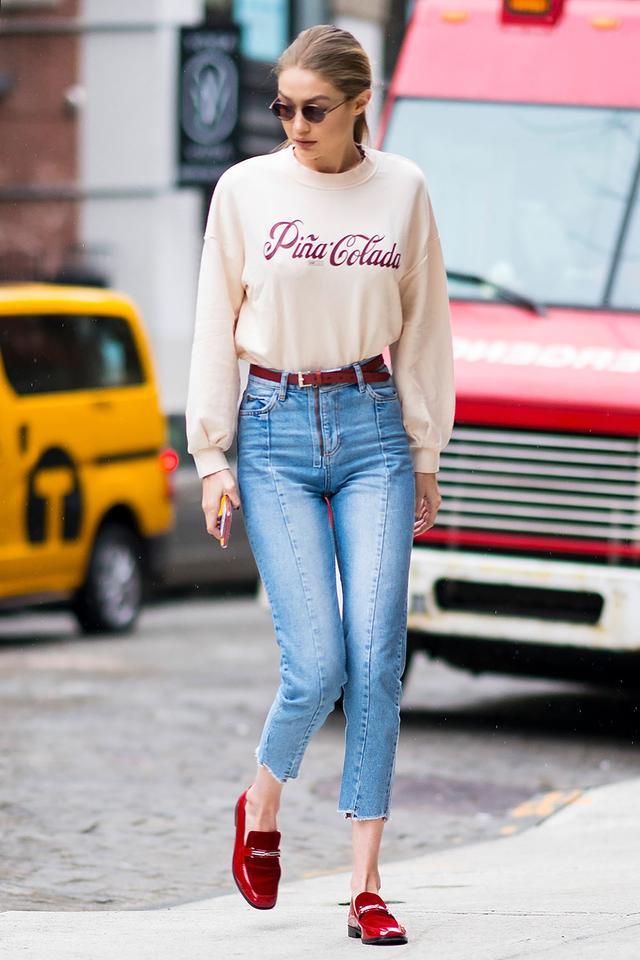 Gigi Hadid in a Pina Colada sweatshirt and blue jeans