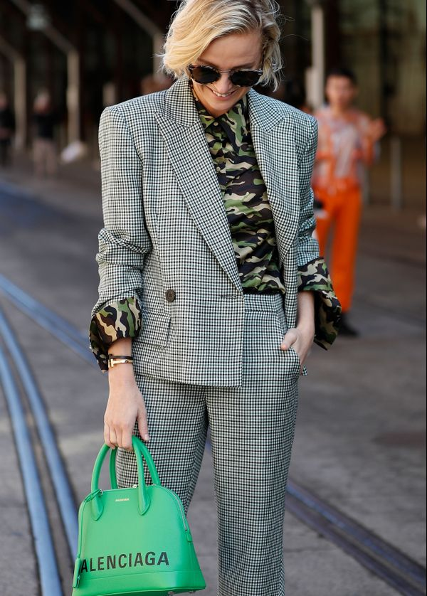 WHO: Nadia Fairfax STYLE TIP: We love how Nadia's bright green Balenciaga bag puts an unexpected twist on her classic checked blazer, highlighting the green in her camo button-up.