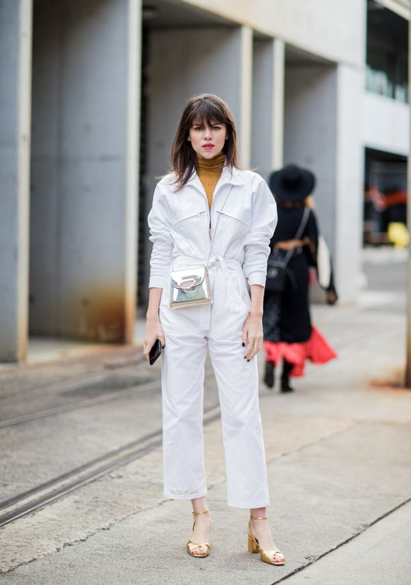 STYLE TIP: The silver bag and mustard turtleneck upgrade this white boiler suit into a complete look.