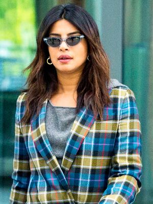 Priyanka Chopra Lands at the Airport for the Royal Wedding in an Epic Pantsuit