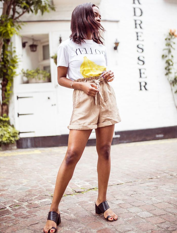 Summer Holiday Outfit Ideas: Eni in a pair of beige shorts and a printed tee