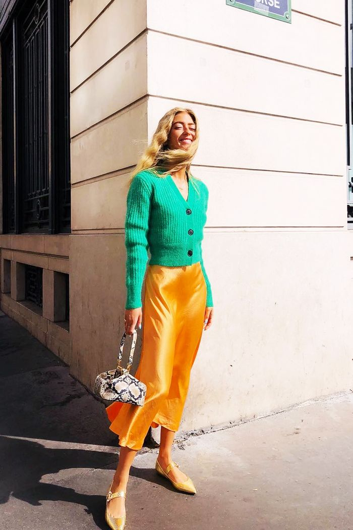 Best slip skirts: Emili Sindlev wearing orange slip skirt and green cardigan