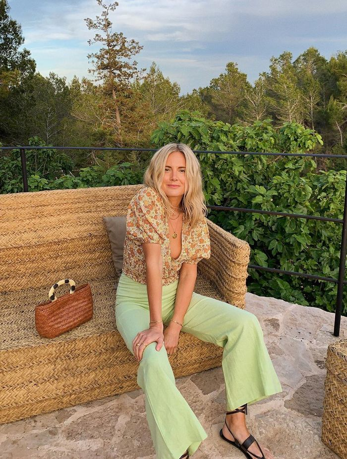 What to Wear in July: Lucy Williams wears a pair of pastel trousers and a floral top