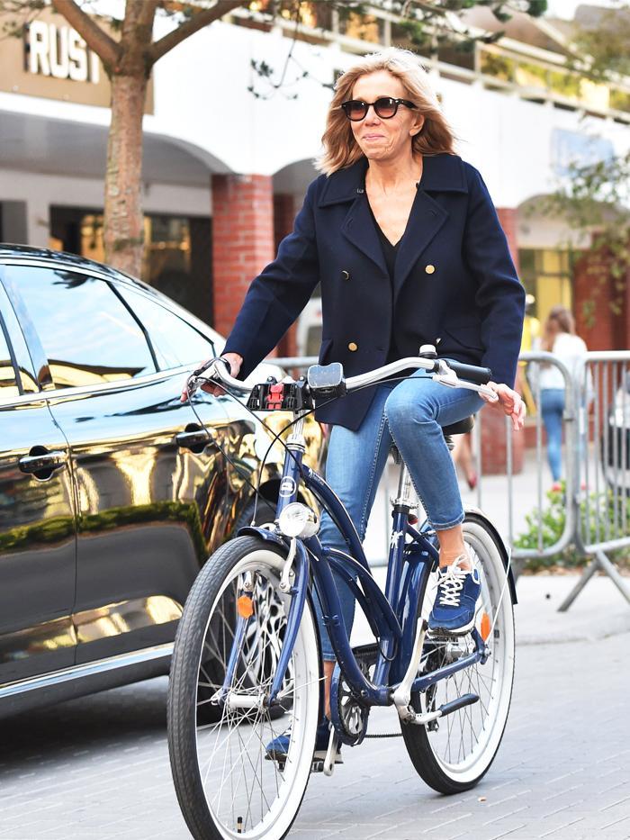 Brigitte Macron style:  Brigitte rides a bike wearing jeans and a pea coat