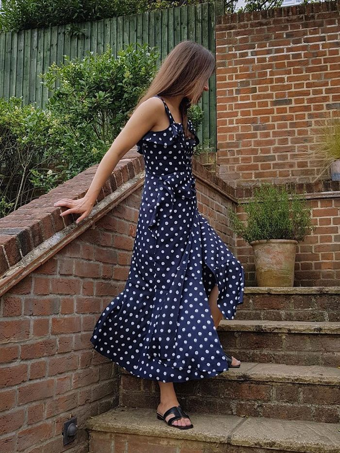 dune loupe sandals: penny goldstone wearing a pair of dune sandals and a polka dot dress