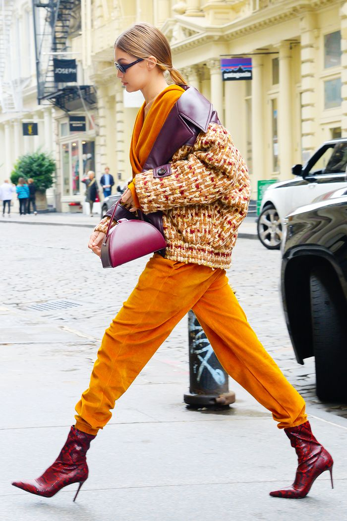 Gigi Hadid snakeskin boots: Gigi wearing orange trousers, woven jacket and Mango boots