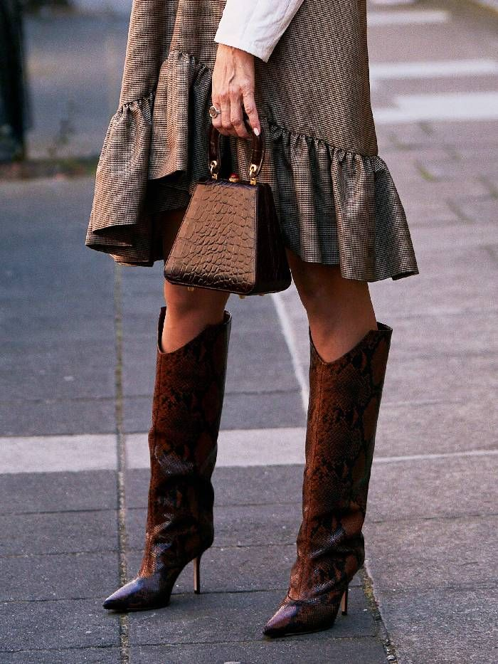 Showgoer wears snake-print knee high boots with a grey dress for fashion shows