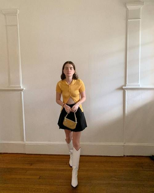 Pleated Skirt Outfits: Molly wears a black pleated mini skirt with a yellow knit and white boots