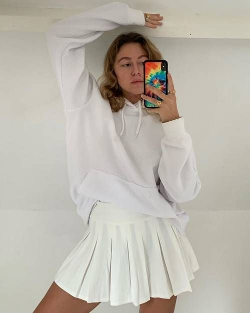 Pleated Skirt Outfits: Elise wears a white pleated tennis skirt with a hoodie and chunky rings