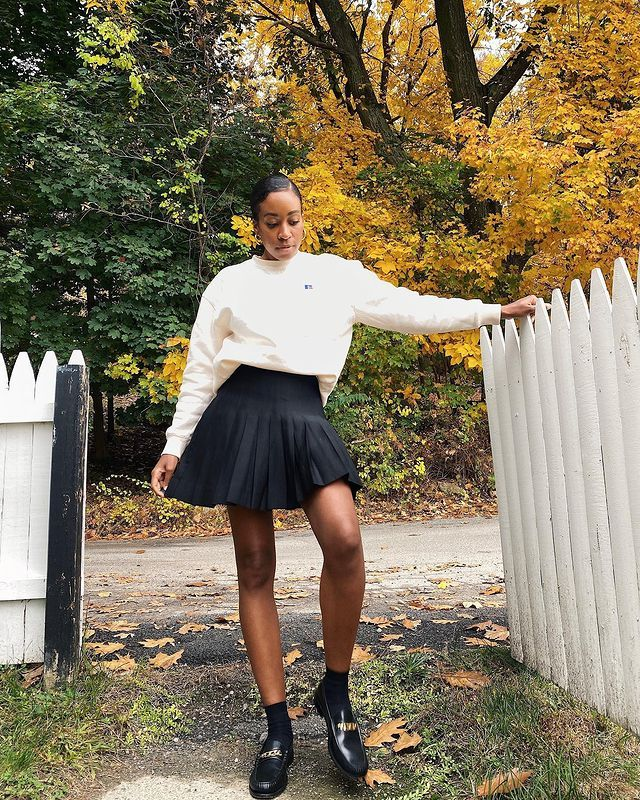 Pleated Skirt Outfits: Chrissy wears a black pleated mini skirt with a cream sweatshirt and loafers
