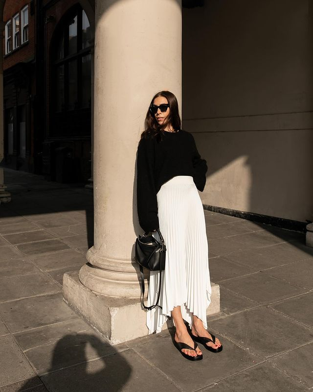 Pleated Skirt Outfits: Jess wears a white pleated skirt with a black knitted jumper and accessories