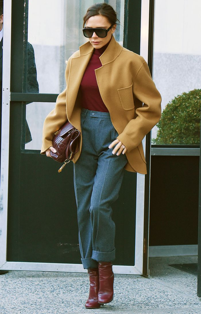 Celebrity winter outfits: Victoria Beckham wearing a short camel coat, blue trousers, burgundy roll neck, and matching bag and boots.