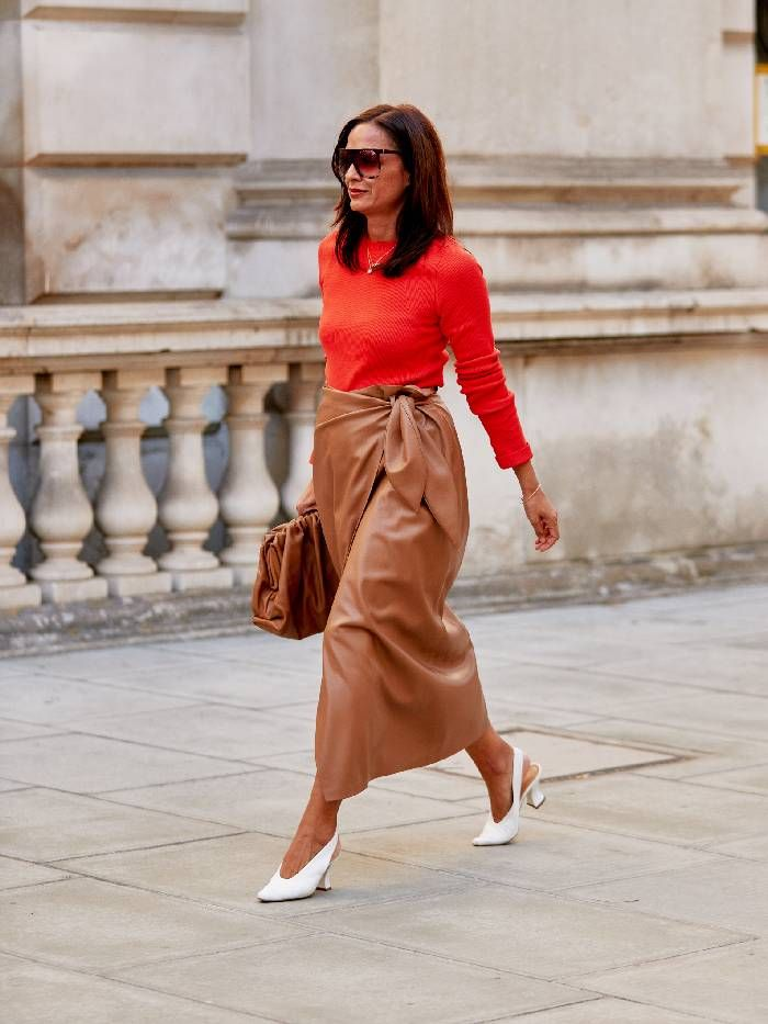 Showgoer wears red fine knit tucked into a leather midi skirt with white heels.