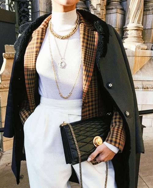 Layering jacket and coat: Ana Vitiello wearing black coat and checked blazer