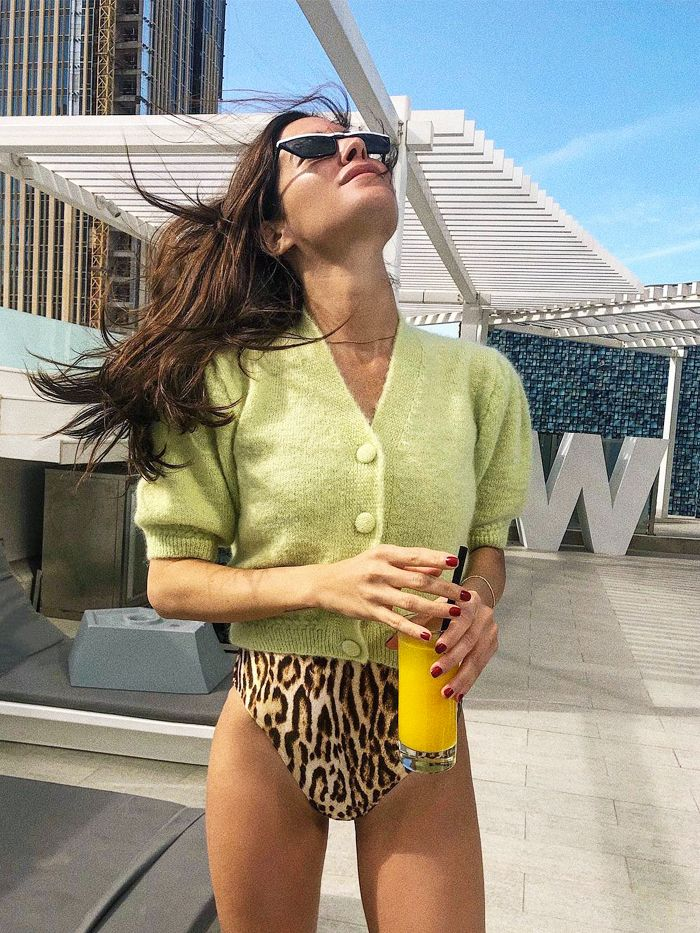 2019 fashion staples: Gala Gonzalez in a green cardigan with a leopard swimsuit