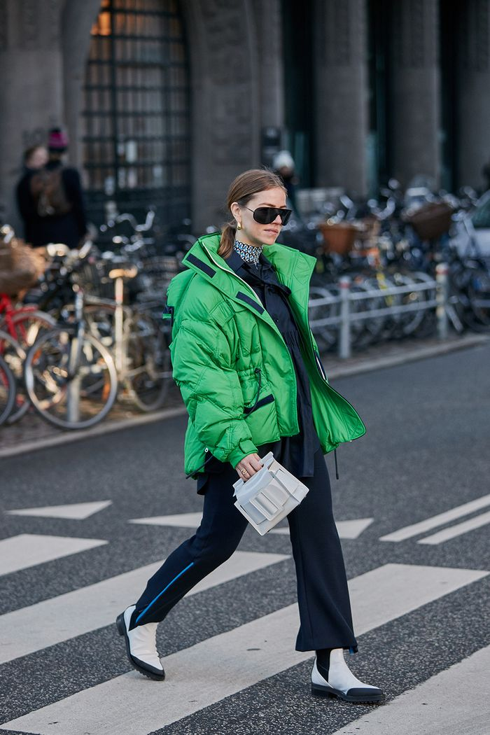 Copenhagen fashion week street style January 2019: a green puffer coat worn with black tailoring